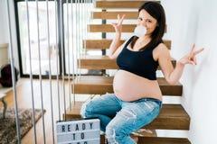 Portrait gai de la jeune femme enceinte s'asseyant sur des escaliers appréciant la vie détails modernes de mode de vie - nouveau  Images stock
