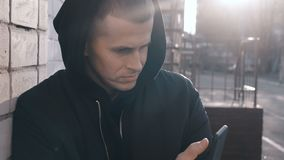 Portrait of young man gangster drug dealer in the hood uses a smartphone outdoor urban background stock footage