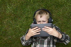 Portrait garçon blond d'enfant du jeune jouant avec une tablette numérique se trouvant dehors sur l'herbe Photo libre de droits