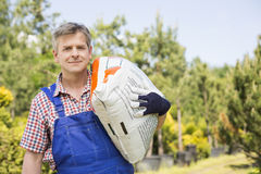 Portrait of gardener carrying sack in plant nursery Stock Photos
