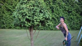 The gardener is trimming a tall bush. Portrait of a gardener girl trim a tall bush with a trimmer stock footage