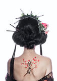 Portrait of a geisha from back. Figure cherry and hieroglyphs. Royalty Free Stock Image