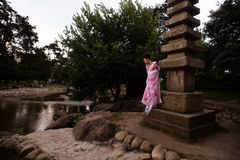Portrait of geisha girl in tender pink kimono posing in park Stock Image