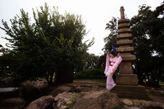 Portrait of geisha girl in tender pink kimono posing in park Royalty Free Stock Images