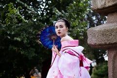 Portrait of geisha girl in tender pink kimono posing in park Stock Images