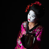 Portrait of geisha presenting something Stock Photography