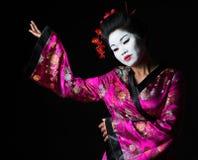 Portrait of geisha showing on something Royalty Free Stock Image