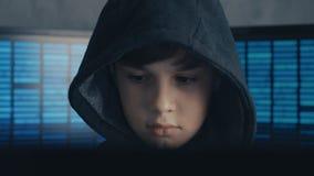 Portrait of a Genius Boy Hacker Prodigy in the hood working on computer in secret data center
