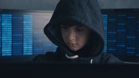 Portrait of a Genius Boy Hacker Prodigy in the hood working on computer in secret data center