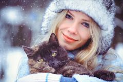 Portrait of a gentle glamorous woman in a winter hat with a catsnow falls in cold tones, love of animals. Portrait of a gentle glamorous woman in a winter hat royalty free stock photo