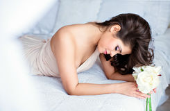 Portrait of a gentle sensual girls brunette lying on a white bed. In a beige dress with a flower in hand Stock Photos
