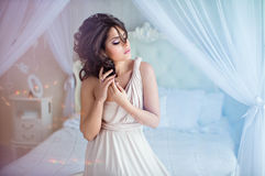 Portrait of a gentle sensual girls brunette sitting on a white b. Ed Royalty Free Stock Photos