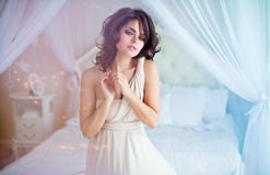 Portrait of a gentle sensual girls brunette sitting on a white b. Ed in a beige dress Stock Images