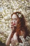 Portrait of A gentle woman with long red hair in a blooming spring garden. Red-haired sensual girl with pale skin and stock photo