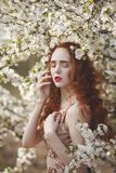 Portrait of A gentle woman with long red hair in a blooming spring garden. Red-haired sensual girl with pale skin and royalty free stock photos