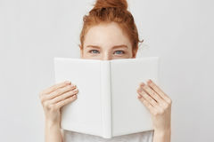 Portrait of ginger girl hiding behind book looking at camera. Stock Photo