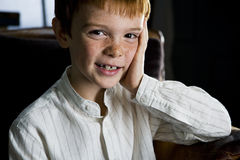 portrait of ginger haired boy leaning face on hand Royalty Free Stock Image