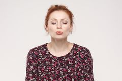 Portrait of ginger woman,closed eyes and send air kissing at cam. Era. Studio shot, isolated on gray background Stock Photography