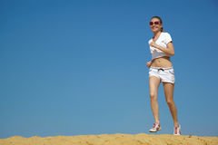 Portrait of the girl. Girl runs on sand against the dark blue sky Stock Photography
