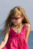 Portrait of a girl. Yuong blonde girl in pink dress and sunglasses near ocean. Portrait Royalty Free Stock Photo