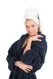 Portrait of the girl. The girl in a dark blue dressing gown and a towel on a head, isolated on a white background Stock Photography
