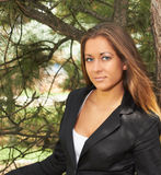 Portrait girl. Young girl in a black jacket near the tree Stock Photos