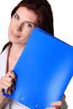 Portrait of the girl. The beautiful young girl smiles with a dark blue folder in a hand Royalty Free Stock Photography