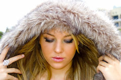 Portrait of a Girl. Fashion portrait of a young woman in a hooded fur jacket Royalty Free Stock Photography