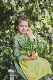 Portrait of a girl against the backdrop of flowering trees 8268. The child holds a tub of sprouted leek Royalty Free Stock Photos