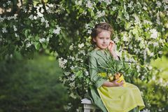 Portrait of a girl against the backdrop of flowering trees 8267. The child holds a tub of sprouted leek royalty free stock image