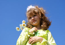 Portrait of the girl against the sky. The happy girl smiles and holds in a hand a bouquet from camomiles against the sky in the summer Royalty Free Stock Photography