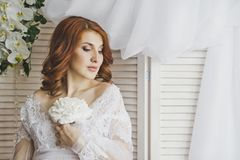 Portrait of a redhead girl in a gentle insolation 6884. Portrait of girl against white wooden blinds Stock Photos