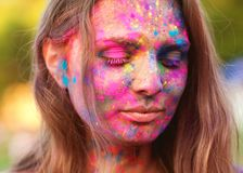 Portrait of a girl all face in paint celebrate a festival of paints holi. Girl celebrates holi festiva royalty free stock image