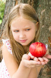 Portrait of a girl with apple. Portrait of a cute little girl holding red apple outdoors Royalty Free Stock Photography