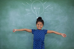 Portrait of girl with arms outstretched by bulb drawing on wall. Portrait of girl with arms outstretched standing by bulb drawing on wall stock photo