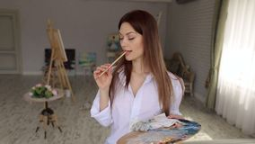 Portrait of a girl artist with paintbrushes in hand, she thinking what to draw. stock video footage