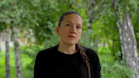 Portrait of a girl on a background of green foliage of birch trees in the summer. Russian young woman with braid in a black dress standing and looks at the stock video footage