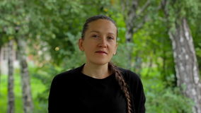 Portrait of a girl on a background of green foliage of birch trees in the summer. Portrait of a smiling girl on a background of green foliage of birch trees in stock video footage