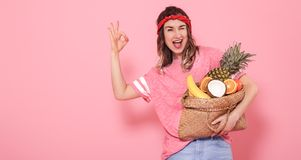 Portrait of a girl with a bag with fruit isolated on a pink background stock photography