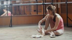 Portrait of a girl balerina dancer putting on her ballet shoes