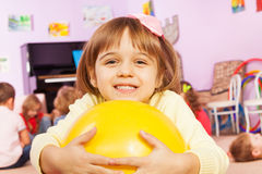 Portrait of girl with ball and friends on back Stock Images