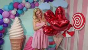 Portrait of girl with balloons in room with candy. Cute funny girl in pink striped dress with red gel balloons at candy party. Barbie style stock video footage