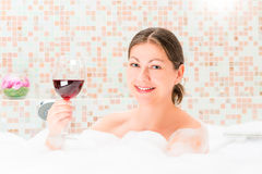 Portrait of a girl in a bath with a glass of drink Stock Image