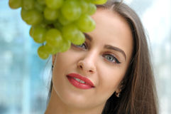 Portrait of a girl behind a bunch of grapes Royalty Free Stock Photos