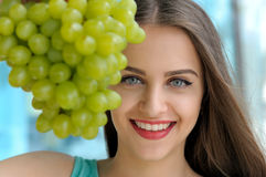 Portrait of a girl behind bunch of ripe grapes Stock Image
