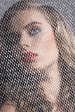 Portrait of girl behind net turned at right Stock Photo