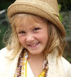 Portrait of a girl in a beige hat, white blouse and with different beads around her neck royalty free stock images