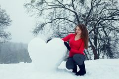 Woman with a big snowy heart Royalty Free Stock Image