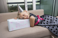 Portrait of girl with birthday gift lying on sofa at home Stock Photo
