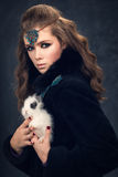 Portrait of a girl in a black fur coat with a white rabbit. Royalty Free Stock Images